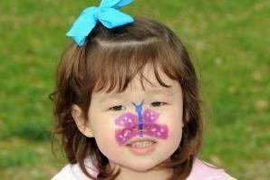 Young girl with butterfly painted on face.
