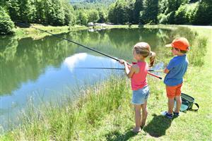 boy and girl fishing in pond